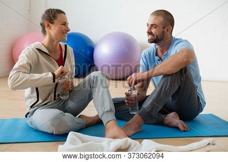 Instructor and female student talking while having water in yoga studio