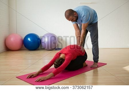 Instructor assisting student in doing child pose at yoga studio