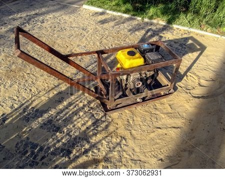 Home-made Vibratory Rammer Stands On A Site With Newly Laid Granite Paving Stones. Do-it-yourself Co