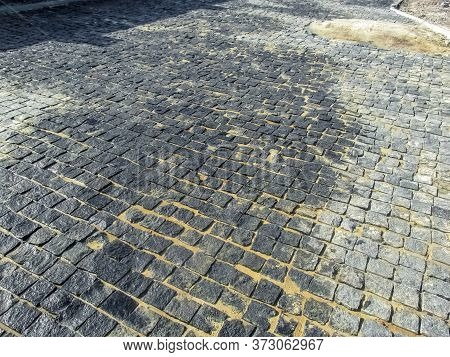The Road On The Street Paved With Gray Granite Cobbles. Newly Laid Paving Tiles At The Site. The Res