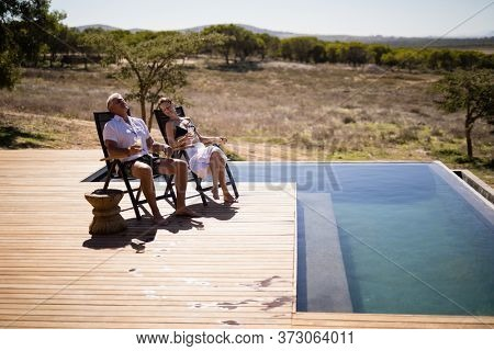 Couple relaxing while having a glass of drink near poolside