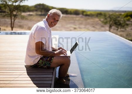 Portrait of smiling man using laptop near poolside during safari vacation