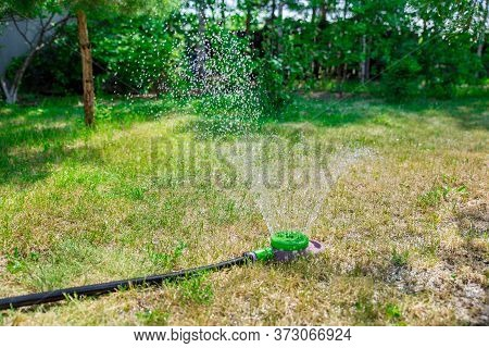 Watering The Green Grass In The Park. Watering The Lawn Of A Private Home Using An Irrigation System
