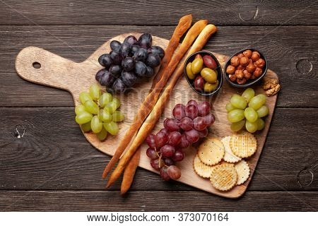 Grapes, nuts, bread sticks and olives antipasto. Appetizer selection on wooden board. Top view. Flat lay