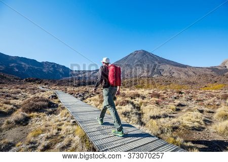 Man walking on hike trail route with Mount Cook National Park, beautiful mountains region. Tramping, hiking, travel in New Zealand.