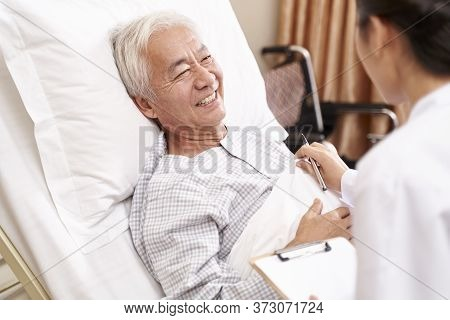 Asian Old Man Lying In Bed Talking To Young Female Doctor In Hospital Ward