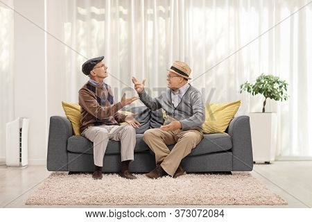 Two elderly man sitting on a sofa inside a house and gaving an argument