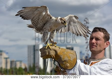 A Man With A Falcon On His Hand In Slavic National Clothes At The Festival Of Slavic Culture, Timed