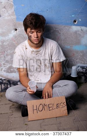 Dirty young homeless guy asking for help, sitting on a street