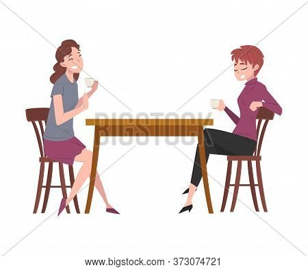 Two Girls Sitting At Table In Cafe, People Drinking Coffee And Relaxing At Coffeehouse Or Coffee Sho