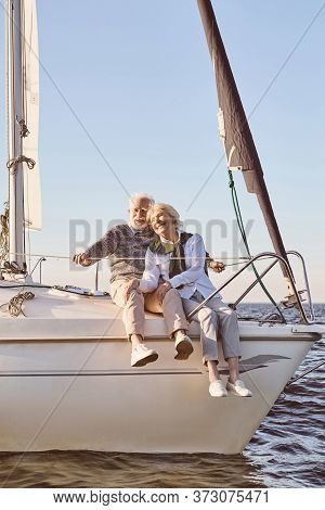 Happy Senior Couple Sitting On The Side Of Sail Boat Or Yacht Deck Floating In Sea. Man And Woman En