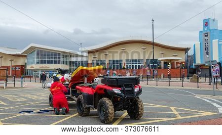 New Brighton, Uk: Jun 3, 2020: A Female Rnli Lifeguard Secures A Rescue Jet-ski To A Trailer Which I