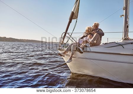 In Love With Sailing. A Happy Senior Couple Sitting On The Side Of A Sail Boat On A Calm Blue Sea. M