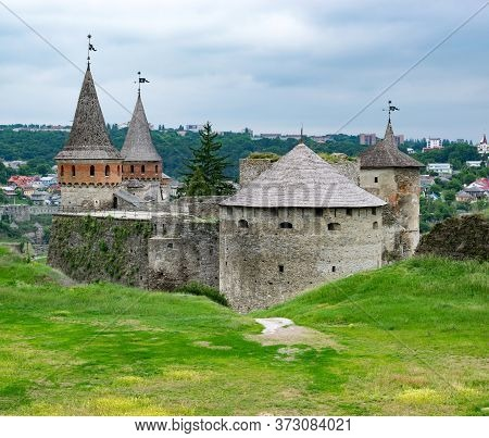 Ancient European Castle. Fortress With High Moss-covered Defensive Walls And Towers. Architectural M