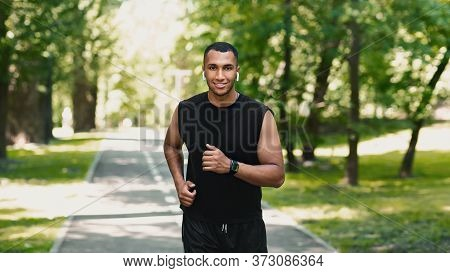 Smiling Young Runner Training On Jogging Track In Beautiful Green Park, Panorama