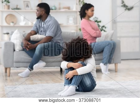 Family Conflicts. Little Unhappy Kid Sitting Alone On Floor After Parents Arguing At Home, Selective