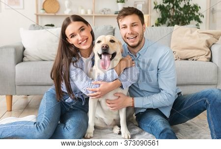 Bonding Concept. Beautiful Young Family Embracing Labrador Sitting On The Floor At Their New Home