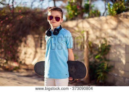 Boy With Skateboard And Earphone On The Street. Childhood, Leasure And Lifestyle Concept