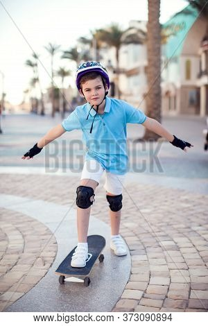 Boy With Skateboard On The Street. Childhood, Leasure And Lifestyle Concept