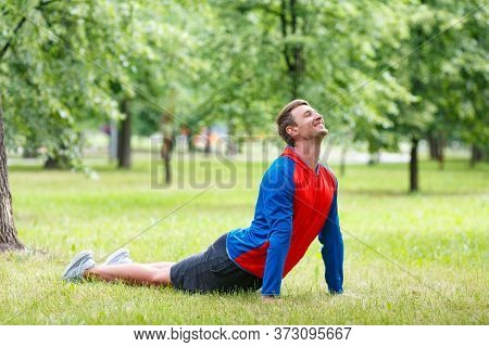 Yoga Man In Cobra Upward Facing Dog Pose Stretching Abs Stomach Muscles. Fit Male Sports Model Doing