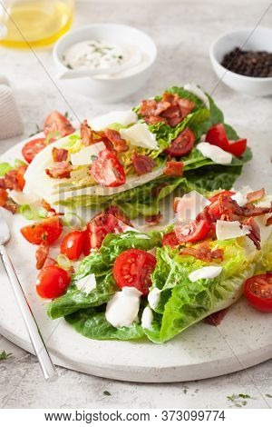 romaine lettuce topped with bacon tomato parmesan, sauce. healthy keto paleo diet lunch
