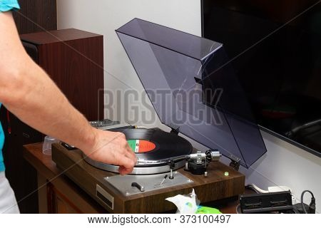 Vinyl Record Player On A Wooden Table. Man's Hand Turns On The Player. Sound Technology For Djs To M