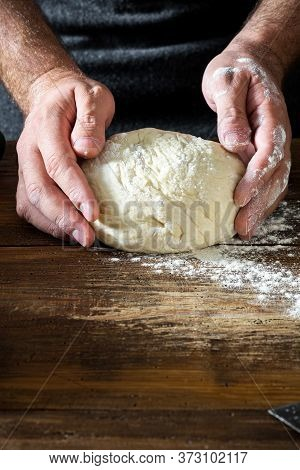 Man Preparing Bread Dough On Wooden Table In Bakery Close Up