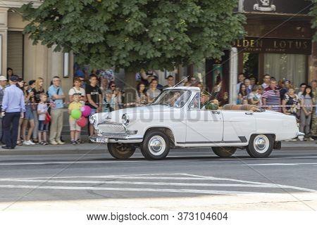 Donetsk, Donetsk People Republic, Ukraine - June 24, 2020: White Volga Cabriolet With A Serviceman A