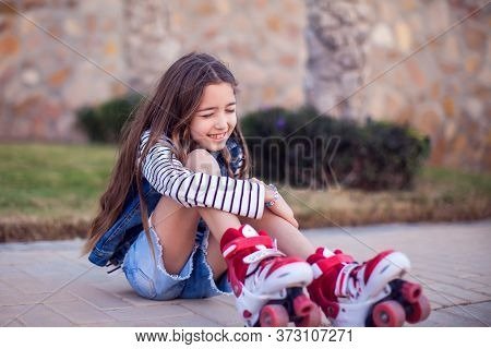A Kid Girl On Rollerskates Fell Down And Feels Pain. Children, Activity And Healthcare Concept