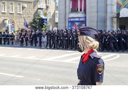 Donetsk, Donetsk People Republic - June 24, 2020: Lovely Policewoman In Foreground In Mask From Coro
