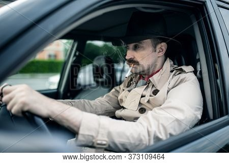 Detective or gangster waiting for someone in his car