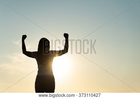 Woman With Fist In The Air During Sunset Sunrise Mountain In Background. Stand Strong. Feeling Motiv