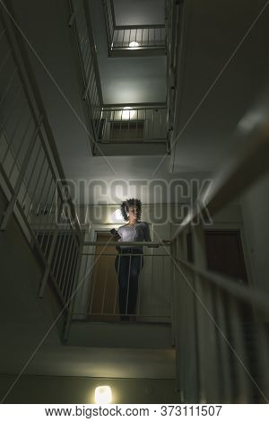 Young Woman Standing On A Low Light Staircase In A Building Hallway, Listening To The Music; Woman W