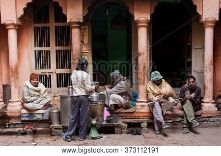Varanasi, India: Group Of People Sitting On Indian Street And Drinking Tea Masala With Spices At Mor