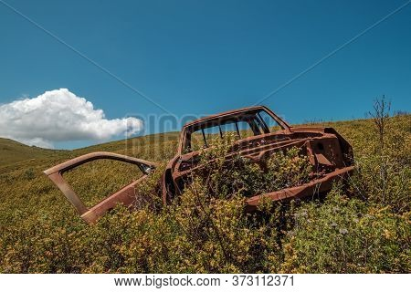 A Rusting And Burnt Out Abandoned Utility Vehicle Slowly Being Consumed By The Wild Maquis In The Mo