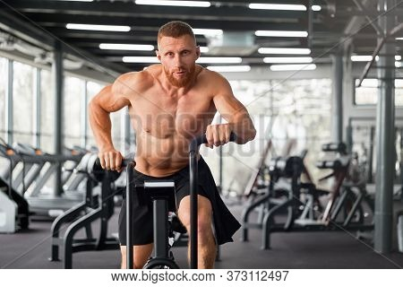 Man Exercise Bike Gym Cycling Training Fitness. Fitness Male Using Air Bike Cardio Workout. Athlete