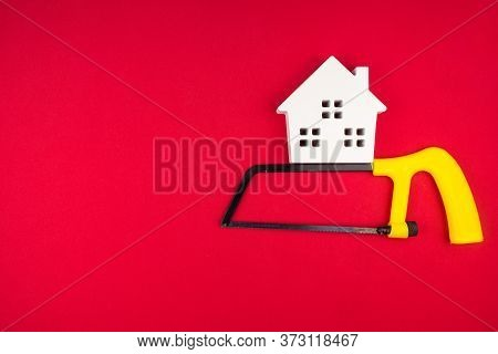 Wooden White House And Metal Saw On Red Background With Copy Space.real Estate Concept, New House Co