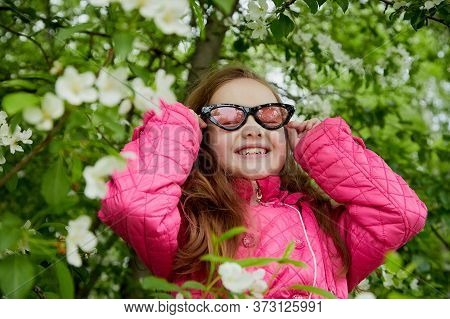 Pretty Cute Little Girl With Long Hair And In Pink Glasses Posing Near A Blooming Apple Tree With Wh