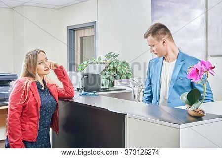 Beautiful Girl Flirts At Work With Office Manager At The Reception