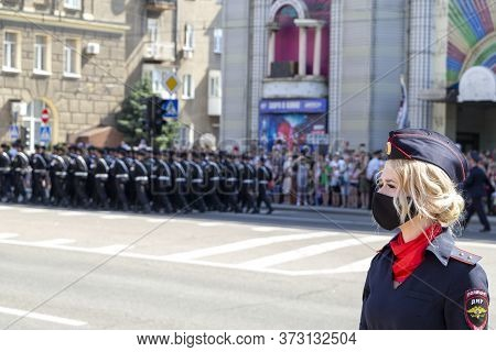 Donetsk, Donetsk People Republic - June 24, 2020: Policewoman In Foreground In Mask From Coronavirus