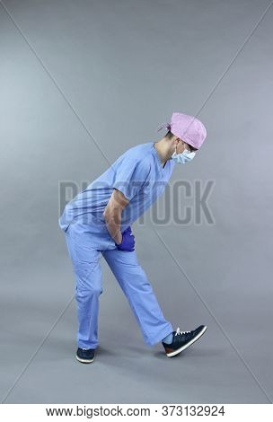 Exercise for medic, nurse,  dentist in standing position.Caucasian mant in uniform, mask and eyeglasses , stretching body   in studio - healthy lifestyle at work.