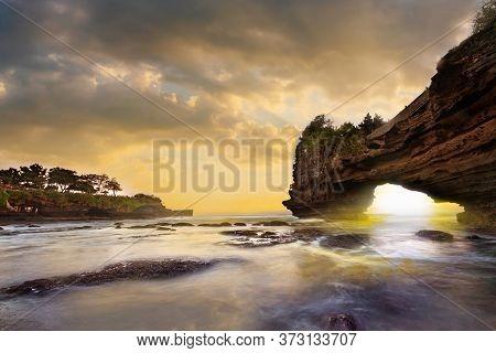 Sunset Near Famous Tourist Landmark Of Bali Island. Tanah Lot & Batu Bolong Temple. Long Exposure Ef
