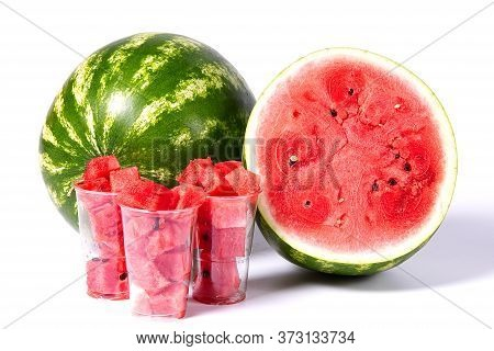 Sliced Red Watermelon Cubes In Plastic Cup A Front Of Fresh Organic Green Watermelon And Sliced Half