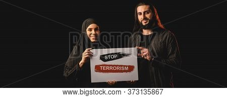 Panoramic Orientation Of Smiling Muslim Couple Holding Card With Stop Terrorism Lettering Isolated O