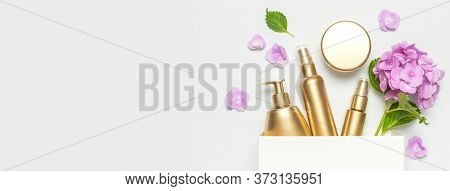 Cosmetic Mock Up Gold Bottles. Cosmetics, White Gift Bag, Pink Hydrangea Flowers On Light Background