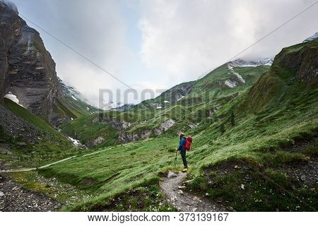 Man Tourist With Backpack Standing On Rocky Mountain Path In Green Hillside Valley. Mountaineer Enjo