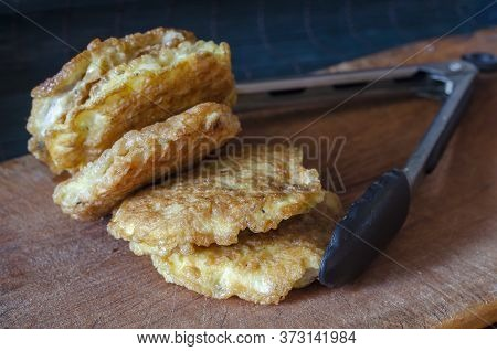 Fried Chops In Batter On A Wooden Cutting Board. Kitchen Tongs And A Serving Of Fried Chops. The Pro