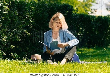 Girl In A Stylish Ijak Holds A Folder. The Concept Of Onlay Work Freelancer Outdoors In A Big City I