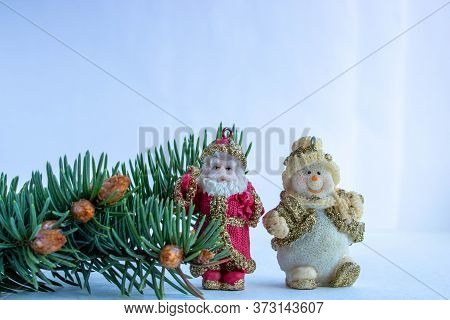 Santa Claus And The Snowman In The Spruce Forest. Cute Toys Next To A Spruce Branch On A White Backg