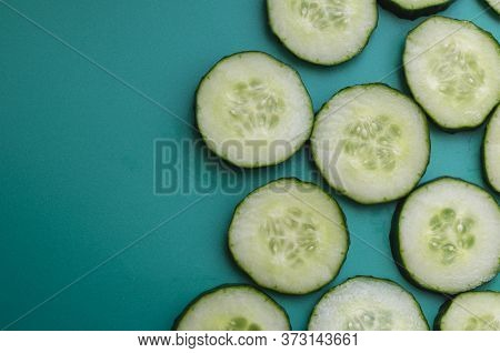 Sliced Cucumber Sliced Across On Turquoise. Fresh Fragrant Cucumber Cut Into Pieces. Health Care, De